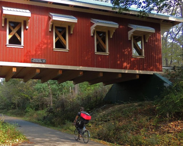 Photo: Cyclist passing under covered bridge on trail. Greene County Cycling Classic.
