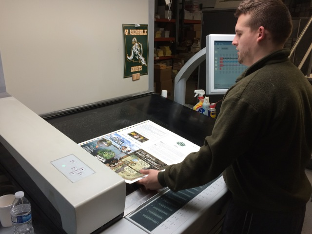 Photo: Pressman Checking First Pages of the 2016 Calendar Just Off the Press - Photo by James Guilford